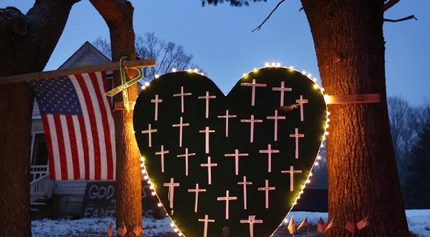 A makeshift memorial with crosses for the victims of the Sandy Hook massacre stands outside a home in Newtown on the one-year anniversary of the shootings.