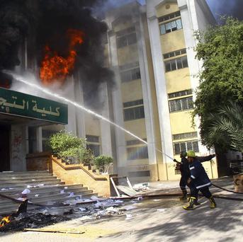 Firefighters put out a blaze inside the faculty of commerce, that was started after a student was killed under disputed circumstances during clashes at a university in Cairo. (AP)