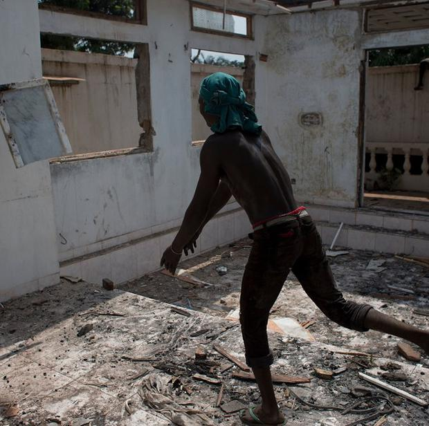 A man smashes a tile against a wall as local residents tear apart a house in Bangui, Central African Republic, amid continued violence in the country.
