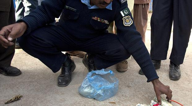 A police officer shows explosives found close to the residence of Pakistan's former president Pervez Musharraf in Islamabad (AP)
