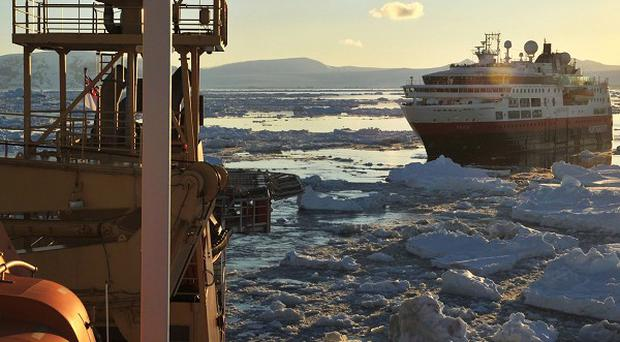 The crew of a research ship trapped in Antarctic ice is awaiting a helicopter rescue. (MoD)