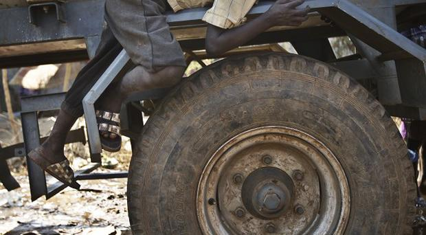 A displaced boy sleeps on the wheel arch of a water truck at a United Nations compound on the outskirts of Juba, South Sudan. (AP)