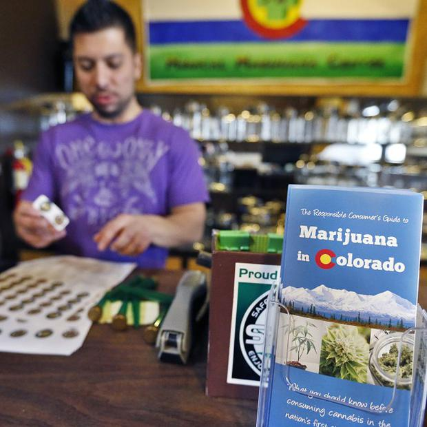 General manager David Martinez labels containers of retail marijuana behind a sales bar fitted with a brochure available to customers at 3D Cannabis Centre in Denver (AP)