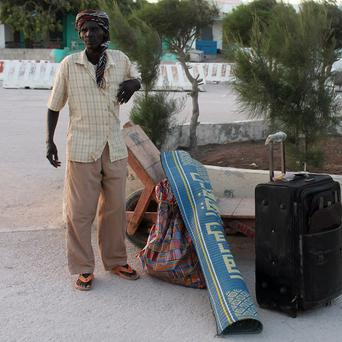 A Somali man who fled from South Sudan's fighting stands with his luggage on his arrival at Mogadishu's International airport (AP)