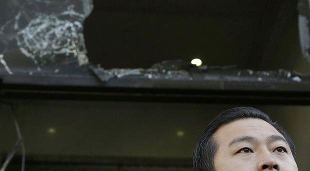 Chinese consulate spokesman Wang Chuan outside the fire-damaged entrance to the building in San Francisco. (AP)