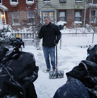 New York City mayor Bill de Blasio talks to reporters while shovelling snow in front of his house. (AP)