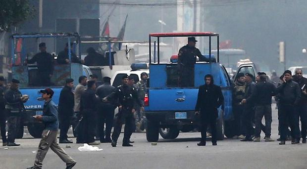 Iraqi security forces gather at the site of a road side bomb attack in central Baghdad (AP)