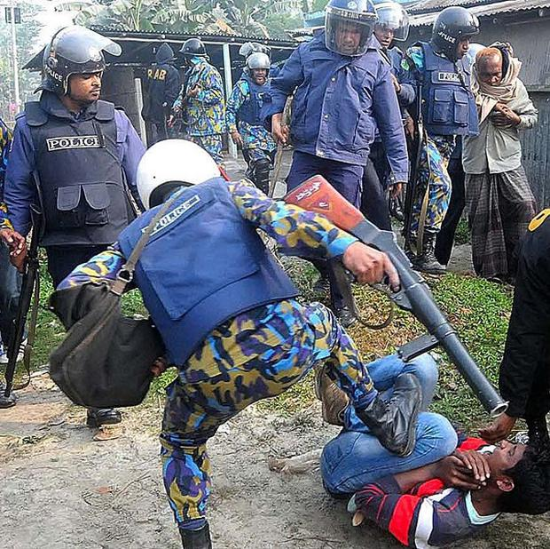 A policeman kicks a suspect following an attack on a polling station in Bogra, north of Dhaka, Bangladesh. (AP)