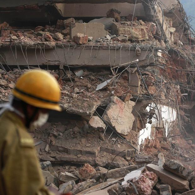 A rescue worker walks past the rubble of a collapsed building in Canacona, India, where the death toll has risen to 17