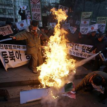 South Korean protesters burn an effigy of Japanese prime minister Shinzo Abe in protest at his shrine visit (AP)