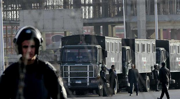 Egyptian security forces stand guard outside a court where Mohammed Morsi is on trial. (AP Photo/Mohammed Abu Zaid)