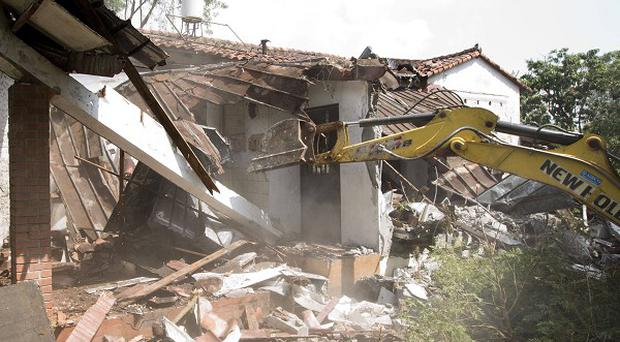 Workers demolish the abandoned mansion of former dictator Manuel Noriega after the Panamanian government found no buyers for it in Panama City (AP)