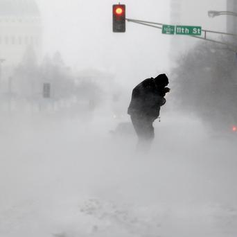 A person struggles to cross a street in blowing and falling snow as the Gateway Arch appears in the distance, in St Louis (AP)