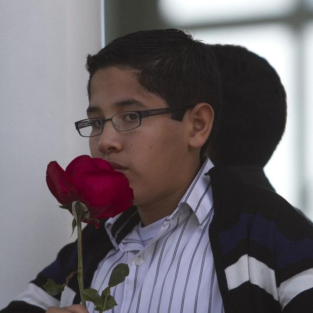A boy holding a red rose stands outside the chapel where a memorial service was held for Monica Spear in Caracas.