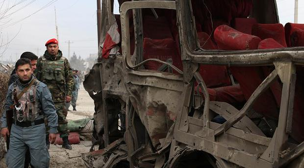 Afghan military forces inspect a suicide attack on a road in Kabul, Afghanistan, after an attacker struck a bus carrying police recruits (AP)