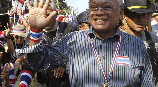 Anti-government protest leader Suthep Thaugsuban, right, waves to supporters during a rally in Bangkok (AP)