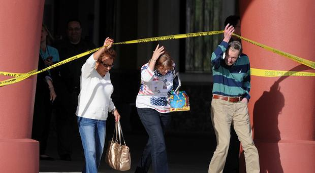 People leave a cinema after a shooting in Florida. (AP/The Tampa Tribune, Cliff Mcbride)