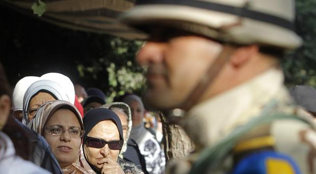 A soldier stands guard as Egyptians line up to vote for a new constitution (AP)