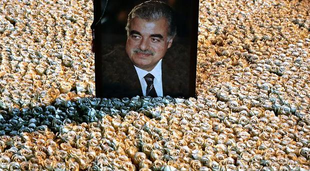 A portrait of assassinated Lebanese Prime Minister Rafik Hariri sits on his grave which is covered by flowers in Beirut (AP)