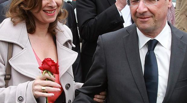 Happier times: Francois Hollande offers a rose to his companion Valerie Trierweiler during his election campaign
