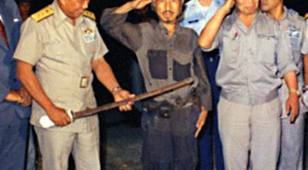 Hiroo Onoda at the Philippines Air Force Base surrendering his sword (Kyodo via AP Images)