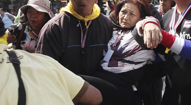 An injured anti-government protester is carried away after a grenade blast at a demonstration in Bangkok