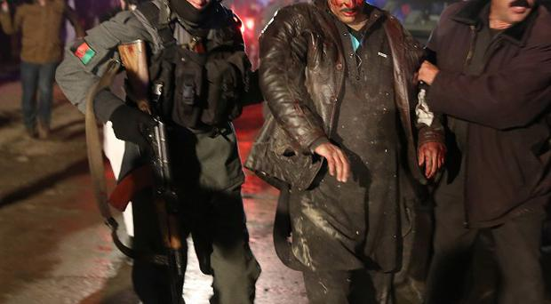 Afghan police forces help an injured man at the site of an explosion at a restaurant in Kabul (AP)