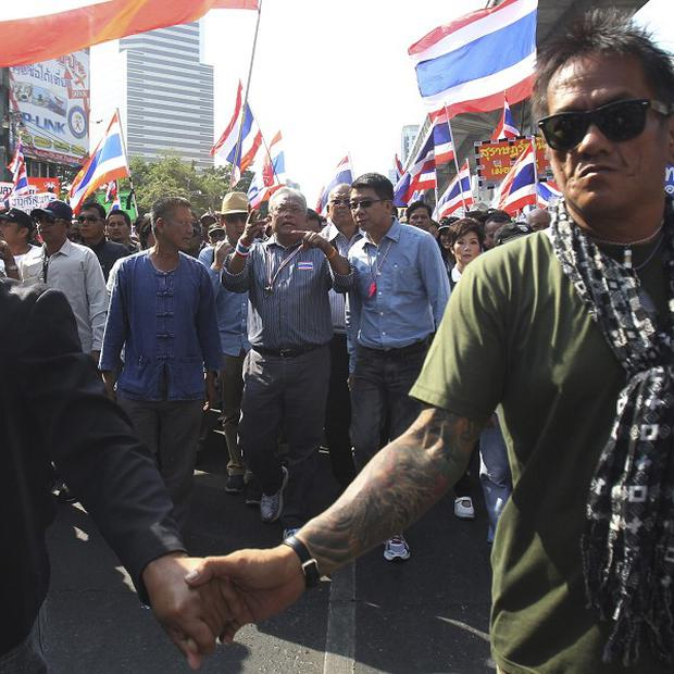 Thai anti-government protest leader Suthep Thaugsuban is guarded as he and other demonstrators march during a rally in Bangkok (AP)