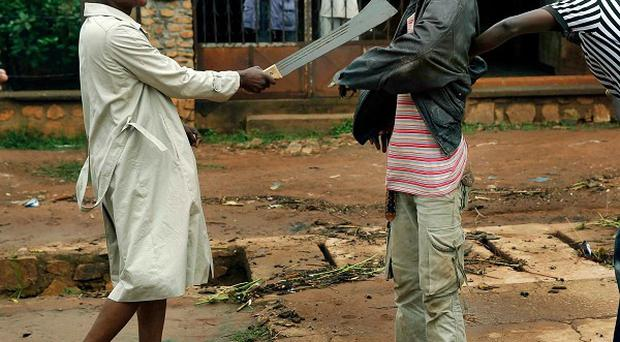 Muslim men organised into militias with machetes rough up a Christian man while checking him for weapons in the Miskine neighbourhood of Bangui (AP)