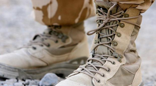 A Nato service member has been killed in an assault by suicide bombers and gunmen in the Zhari district of Afghanistan