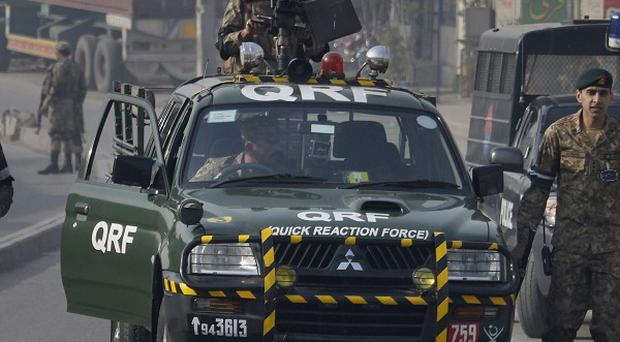 Troops secure a road leading to the site of suicide bombing in Rawalpindi, Pakistan (AP)