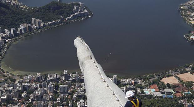 A worker inspects the arm of the Christ Redeemer statue in Rio de Janeiro (AP)