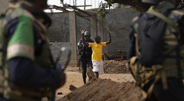 Congolese troops detain a suspected looter in Bangui as violence erupted again in the capital