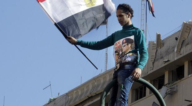 A man waves a national flag at the site of a blast at the Egyptian police HQ in Cairo (AP)