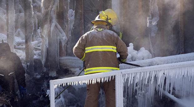 Emergency workers search through the frozen rubble of a care home in Quebec (AP)