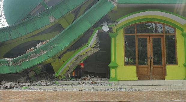 A Muslim woman walks past a mosque that collapsed after a 6.1-magnitude quake rocked Java island, in Banyumas, Indonesia (AP)
