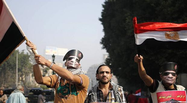 Egyptians wear masks of Egypt's Defence Minister in Tahrir Square in pro-military rallies to mark the anniversary of the uprising
