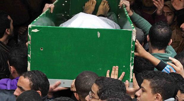 Egyptians carry the coffin of a man killed during clashes between protesters and security forces in Cairo (AP)