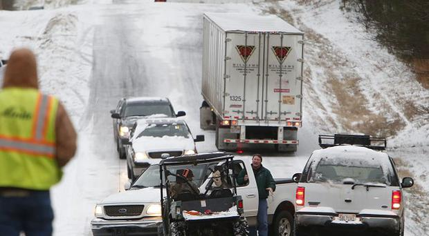 People work to clear stranded vehicles in Wilsonville, Alabama, as a rare snowstorm gridlocked America's South (AP)