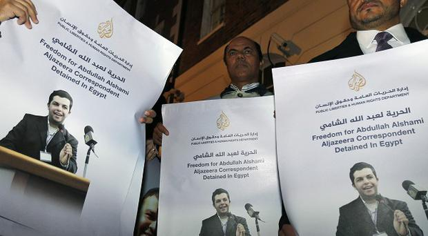 Demonstrators hold pictures of Al Jazeera Arabic network journalist Abdullah Al Shami, one of those held in Egyptian custody (AP)