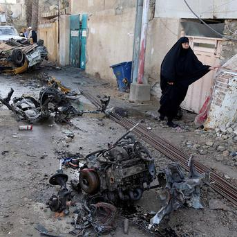 A woman walks through the site of a car bomb attack in the Shula neighbourhood in Baghdad (AP)