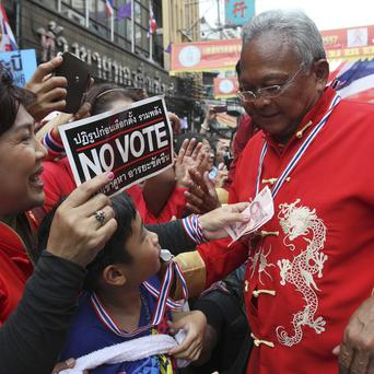 Anti-government protest leader Suthep Thaugsuban is offered donations from supporters during a march through at China Town in Bangkok (AP)