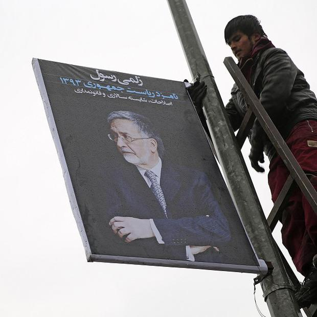 An Afghan hangs an election poster of candidate Zalmai Rasool in Kabul. (AP Photo/Massoud Hossaini)