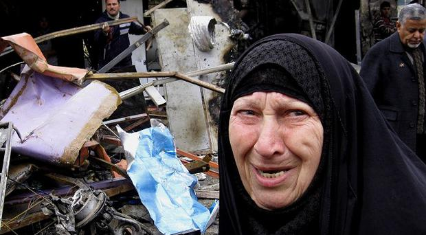 An Iraqi woman looks at damage from a car bomb explosion in Baghdad (AP Photo/Khalid Mohammed)