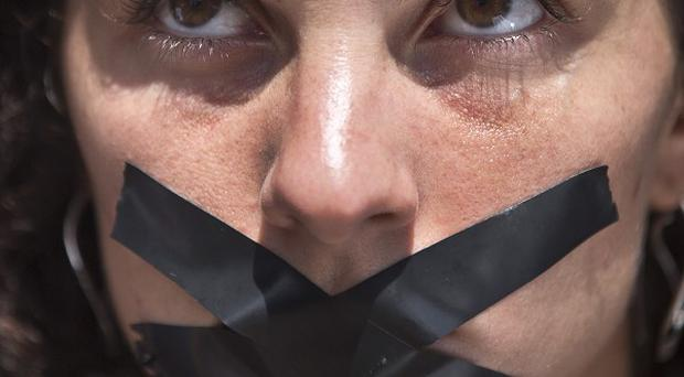 A member of the media sits with black tape across her mouth, signifying the silencing of the media (AP Photo/Ben Curtis)