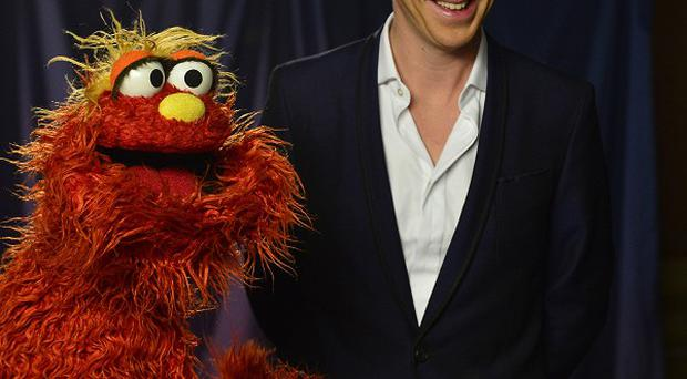 Sesame Street character Murray Monster, left, and actor Benedict Cumberbatch (AP Photo/PBS)