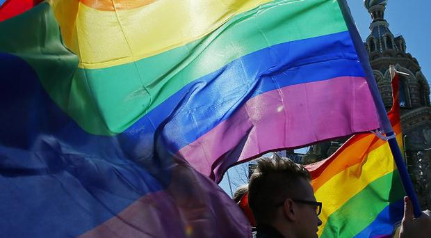 Gay rights activists carry rainbow flags as they march in St Petersburg (AP/file)