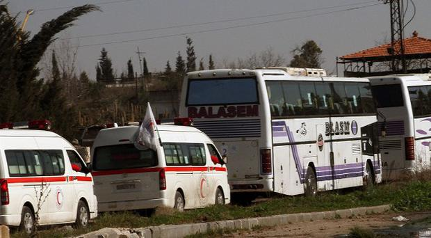 Syrians on two buses followed by the Syrian Arab Red Crescent's vehicles evacuate from Homs before the ceasefire ended (AP)