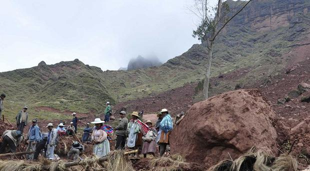 Farmers dig through the mud in search of survivors after a mudslide buried a small settlement in Bolivia (AP)