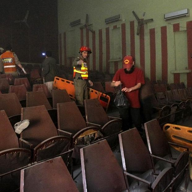Rescue workers examine the site of a grenade attack on a crowded cinema that killed and wounded many people in Peshawar (AP)